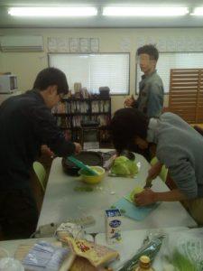 白菜やキャベツ、にらを刻みあんを作ります。後ろのほうでカメラ目線の人がいますがスルーで、刻み続けます。