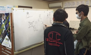 高校生が中学生にホワイトボードを使ってゲーム作りの解説をする様子